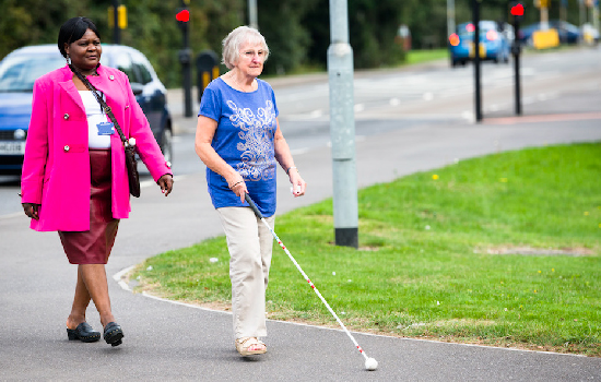 Support worker walking with visual impaired person